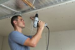 Young man fixing drywall suspended ceiling to metal frame using electrical screwdriver. royalty free stock image