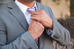 Young man fixing his tie Royalty Free Stock Image