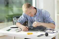 Young man fixing laptop, horizontal Stock Photography