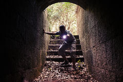 Young man with flashlight enters dark stone tunnel Stock Photography
