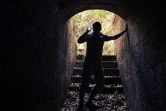 Young man with flashlight enters dark stone tunnel Royalty Free Stock Photography
