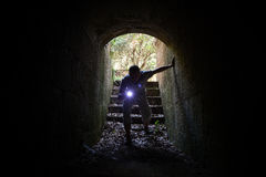 Young man with a flashlight enters the stone tunnel Royalty Free Stock Image