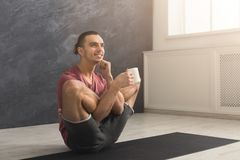 Young man in flexible yoga pose drinking tea. Young smiling man in flexible yoga pose drinking tea, sitting on mat at gym and practicing twisting exercise, copy Stock Photography