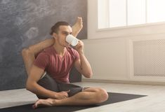 Young man in flexible yoga pose drinking tea. Young sporty man in flexible yoga pose drinking tea, sitting on mat at gym and practicing twisting exercise, copy Royalty Free Stock Photos