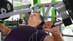 Young man flexing chest muscles on gym machine.  stock video footage