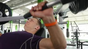 Young man flexing chest muscles on gym machine.  stock footage