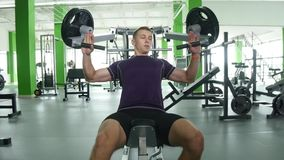 Young man flexing chest muscles on gym machine Royalty Free Stock Image