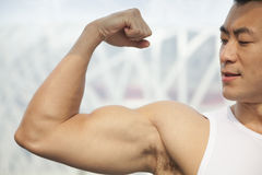 Young man flexing his bicep Stock Image