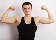 Young man flexing his muscles. Portrait of a handsome young man showing off his muscles Royalty Free Stock Images