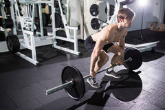 Young man flexing muscles with barbell in gym. Sport Stock Photo