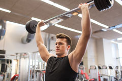 Young man flexing muscles with barbell in gym Stock Photo