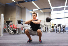 Young man flexing muscles with barbell in gym Stock Photos