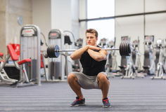 Young man flexing muscles with barbell in gym Royalty Free Stock Photography