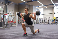 Young man flexing muscles with barbell in gym Royalty Free Stock Image