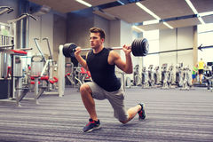 Young man flexing muscles with barbell in gym Royalty Free Stock Images