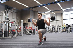 Young man flexing muscles with barbell in gym Stock Images
