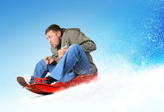 Young man flies on sled in the snow Royalty Free Stock Photo