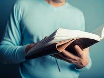 Young man flipping through big book Royalty Free Stock Photo