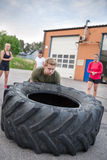 Young man flipping heavy tires outdoor Stock Photography
