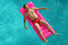 Young man floating on a mattress in water pool Royalty Free Stock Photography