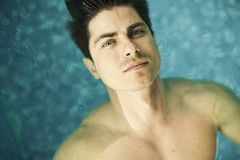 Young man floating in the swimming pool Stock Images