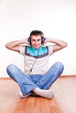Young man on the floor with earphones Stock Photo