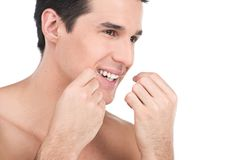 Young man flossing his teeth isolated on white background. Royalty Free Stock Photography