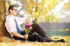 Young man with flowers - expecting someone Royalty Free Stock Photography