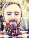 Young man with flowers in his beard  natural blurred background close up Stock Images