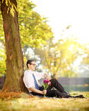 Young man with flowers sitting on grass and checking the time, i Royalty Free Stock Photo
