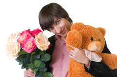 Young man with flowers and teddy bear Royalty Free Stock Photography