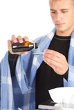 Young man with flu taking syrup Stock Images