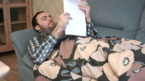 Young man with flu trying to study in bed stock footage