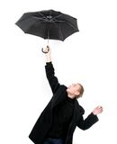 Young man flying away with umbrella Royalty Free Stock Photography