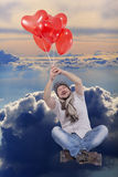 Young man flying on balloons with cloud sky in Stock Photography