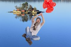 Young man flying on balloons with sea island in Royalty Free Stock Photography