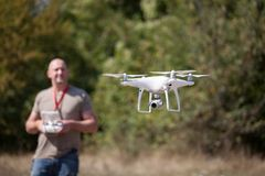 Man with flying drone in the park.  Man with remote controller in his hands taking aerial photos and videos Royalty Free Stock Images