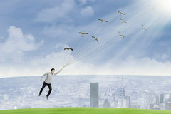 A young man is flying by holding birds Stock Image