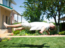 Young man flying or levitating over grass Stock Photos