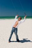 Young Man Flying a Stunt Kite. A young man working the control lines of a stunt kite on the public beach in Treasure Island, Florida Stock Photos