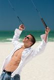 Young Man Flying a Stunt Kite. A young man working the control lines of a stunt kite on the public beach in Treasure Island, Florida Stock Images