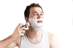 Young man with foam on the face Stock Photos