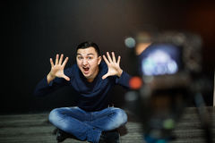 Young man in focus on digital camera screen waving hand while seated on ground against wall for concept about video Stock Photo