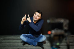 Young man in focus on digital camera screen waving hand while seated on ground against wall for concept about video Stock Image
