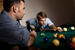 Young man focusing on playing snooker. Young men focusing on playing snooker, concentrating on white ball friend watching at table royalty free stock image