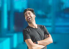 Young man with folded arms laughing looking away. Portrait of young man with folded arms laughing looking away Royalty Free Stock Photo