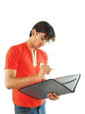 Young man with a folder. A casually dressed young man making notes in the folder he is holding, isolated on white background stock photos