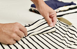 Young man folding clothes. Closeup of a young caucasian man folding a polo shirt, with a pile of folded clothes in the background Royalty Free Stock Photography