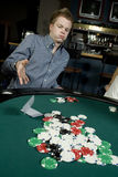 Young man folding during poker game Royalty Free Stock Photo