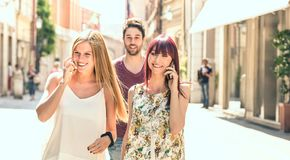 Young man following pretty women while having fun together on city street - Technology concept in everyday lifestyle stock image
